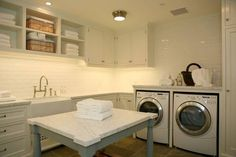 spacious laundry room with clothes folding island