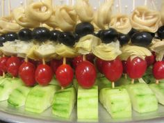 Cheese tortellini on top, black olives (wish we had used the large ones), artichoke hearts, grape tomatoes, all standing in a half circle chunk of cucumber. Drizzled with Balsamic Dressing just before we took each platter out to the table. We put the dressing in a squirt bottle to make the drizzling job easy.
