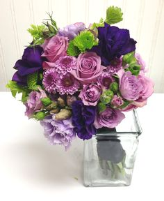 Bridal party bouquet of lavender roses, and buttons, purple lisianthus, and green berries, bells of ireland, and kermit poms. Designed by Rebekah. Seattle Wedding Flowers, Ballard Blossom Inc