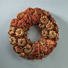 Pumpkin Wreath From CountryDoor. This wreath is bursting with pumpkins of yarn and raffia, all snugly entangled in real vines and leaves.