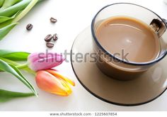 Coffee cup and tulips on white background. Spring flowers and coffee beans. #coffee #spring