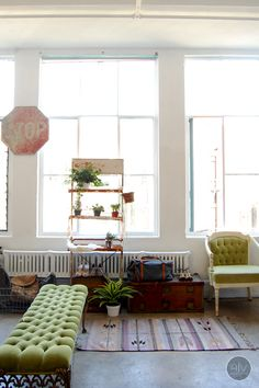 Fresh eclectic/industrial warehouse loft. Love the massive windows, old stop sign and boho rug.
