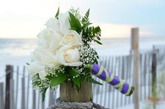 Cream rose bouquet with purple and green wrap.  Photo by Sunset Beach Weddings