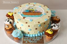 """Noah's Ark Cupcakes #85Religious This cake is a 12"""" round with an edible image of Noah's Ark placed on top. The buttercream dots add some fun to this design. The cake is then surrounded by a dozen custom cupcakes that are decorated with animal faces."""