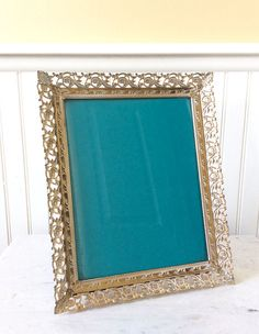Beautiful vintage 8 x 10 ornate picture frame with back easel. Gold whitewashed with a filigree rose design & decorative corner details. In good vintage condition, with original glass. Great for special occasion, wedding, bookshelf, or table top. Measures 11.75 x 9.5 total, fits a 8 x 10 picture Thanks for shopping YellowHouseDecor!  Several picture frames sold separately in shop!  Please visit my sisters shop for more vintage items ( ellansrelics02)