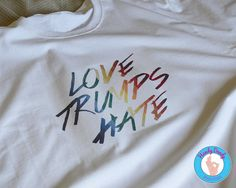"This rainbow-tastic tee shows that love always wins over hate. Our made-to-order shirt features the phrase Love Trumps Hate in rainbow lettering on a white t-shirt. Due to monitor/display settings and/or dye lots, colors may vary slightly.  All of our products are made to order with a professional heat press. If you'd like a different color combination (see image showing our options), include that info in the ""notes to seller"" section when you are making your purchase, otherwise shirt will…"