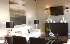 living rooms - gray walls gray abstract art white modern tufted sofa stacked ball crystal lamps black leather brno chairs white black cowhide rug espresso brown media cabinet credenza white vases TV barcelona coffee table polished nickel sconces