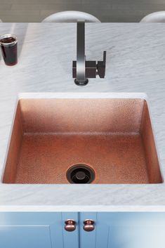 The gorgeous, antique bronze, one-handle bar faucet pairs perfectly with the lustrous copper tones.