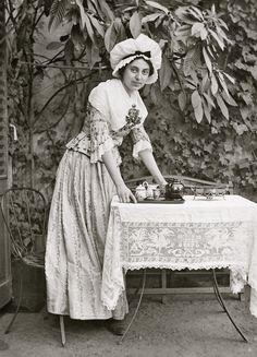 A Maid serving Tea in the Garden, circa 1897.