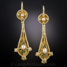A single natural pearl shimmers between a pair of tiny emeralds in the bottom section of these 1 and 5/8 inches long and lovely mid-nineteenth century Victorian earrings, rendered in rich 18K yellow gold. The shapely earrings are accentuated with a beaded outline interrupted with textured foliate sections. The top sections center on a small pearl with textured beads at the cardinal points