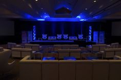 Corporate event meeting featuring white leather soft seating event furniture with custom logo'd tables.