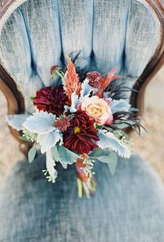 A deep red and orange bouquet of dahlias, astilbe, roses, and dusty miller, created by Southern Blooms by Pat's Floral Design.