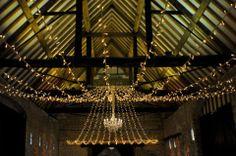 For wow factor, a huge gathered canopy with central chandelier at a barn wedding, lighting by Oakwood Events
