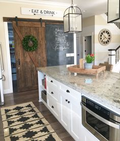 Rustic touches in a modern farmhouse kitchen. It all started with this barn door, made from locally salvaged barn wood, and then the chalk wall was the perfect solution for the wall where the door slides! The clean, white shaker style cabinets balance the