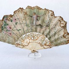 Art Nouveau Fan, Gouache On Silk, Circa 1900 The leaf is silk, it is painted with a woman surrounded by flowers and plants in a typical Art Nouveau style. The mount is carved bone gilded and painted. It measures 10,033 long closed, and about 15,74″ in open diameter.France, Circa 1900.