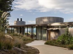 The house is a glazed pavilion siting in the dunescape above a coastal golf links. The two planes of roof and main floor are joined by three timber clad conic forms that house fireplace, bathrooms and kitchen. A partial lower floor is reached by lift and houses guest suite, garage, storage and plant room.