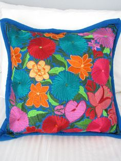 A stunning cotton pillow cover completely woven on the loom and then decorated with embroidered vibrant flowers. CHIAPASBAZAAR.COM