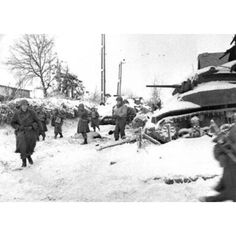 The Battle of the Bulge, which began on December 16, 1944, here's American soldiers from the 117th Infantry Regiment of the U.S. Army's 30th Infantry Division moving past a destroyed American M5 Stuart tank on their march to recapture the town of St. Vith, Belgium during the Battle of the Bulge, in January 1945.