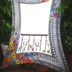#MosaicMirror #Alice in #Wonderland - It sure feels like a doorway Alice's Wonderland. We fell for the #fantasy world, so we created a #floral burst of #rainbow coloured #flowers sprayed on a very #lacy textured border in #white and #grey. This #abstract shape #mirrorframe is created with hand cut #mosaic tiles glass beads on a #plywood base.