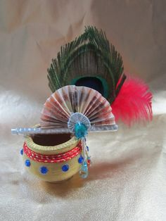 Earthern pot small size with the peacock feather, flute, & a currency note (the fan) with the decorations.