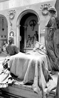 Sculpture of a man seemingly on his death bed while a family member kneels beside him and an angel hovers over him.