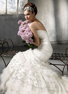 Ivory beaded and embroidered silk organza trumpet bridal gown with pleated tulle ruffle accents, chapel train.