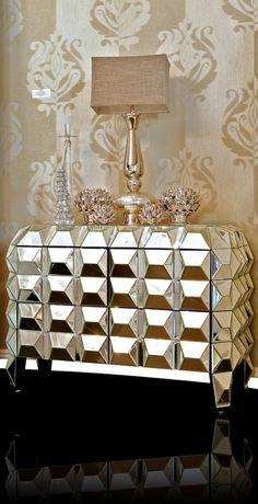 Calling all glamor queens - this nightstand is for you! The many mirrors sitting at different angles catch and reflect the light beautifully, brightening up any room. Four draws with glass knobs sit discreetly in the front, providing the perfect place for you to keep your valuables. The flat, mirrored top also provides space for you to rest your possessions, completing this absolutely fabulous piece.   31 inches (Height) 42 inches (Width) 19 inches (Depth)