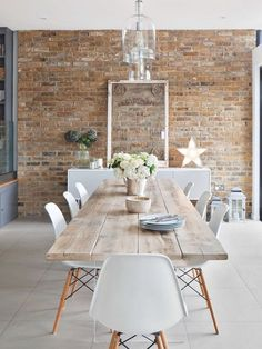 This stunning wooden dining room table brings a element of the coast to this room. The size of it means it could work in an office or kitchen. The white chairs and Scandinavian lighting fixtures complete this look.