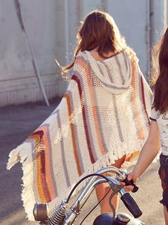 """Summer Breeze Crochet Poncho Boho-inspired open knit poncho with a V-neckline and hood detailing. Asymmetrical hem and statement fringe trim with a front kangaroo pocket.  100% Cotton Hand Wash Cold One Size Length: 22.0"""""""