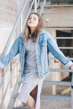 Look minimalista e confortável. O vestido midi cinza com a fenda lateral é leve e fica super lindo com a jaqueta jeans vintage amarrada na cintura. O tênis branco é o querido da vez, sendo do modelo Adidas Superstar.