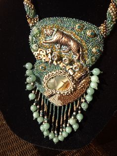Collar detail: natural stones with gold and green seed beads, gold tiger focal, adventurine stones in fringe. Backing is ultra suede.