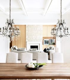 Double chandeliers over a dining table and linen chairs in a white dining room