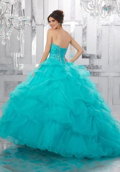 Beautiful Quinceañera Dress Featuring a Tulle Pick-up Skirt with Delicate Beading. A Beaded Sweetheart Bodice Completes the Look. Matching Bolero Jacket Included. Colors Available: Blush, Capri, Fuchsia, White
