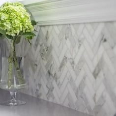 Pretty way to pull in the gray of the kitchen and the white that I love. Calcutta Marble Herringbone tile