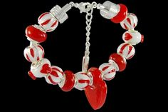 silver plated items: bracelet with lobster, enamel beads, locks. Six glass beads and one glasscharm with 925 silver core.