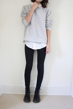 Love the neutral look with the light grey pullover, white button down, black trousers, and black doc martens.