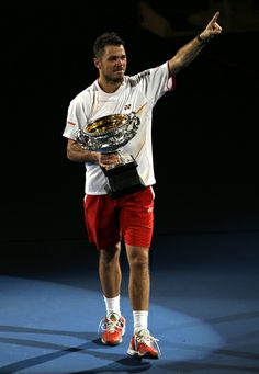 Stanislas Wawrinka of Switzerland walks around the court, with the trophy after defeating Rafael Nadal of Spain in the men's singles final at the Australian Open tennis championship in Melbourne, Australia, Sunday, Jan. 26, 2014. (AP)