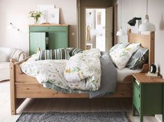 A green bedroom with HURDAL bed in solid wood, SISSELA flowery bed linen and green HURDAL storage.