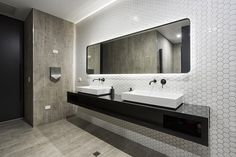Neutral tile or stone floors and accent walls, with sink wall in another accent tile. Like the fun shape of the white sink wall. Black sink countertop. Floating mirror with light behind.