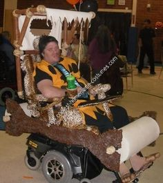 Homemade Fred Flintstone and Flintmobile Wheelchair Costume: My adult son is in a wheelchair and every Halloween I make him a costume and I always try to incorporate his wheel chair into his costume. This year's