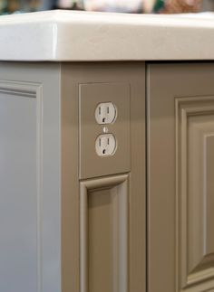 Accessible kitchen electrical outlet at front corner of the cabinet for easy reach.
