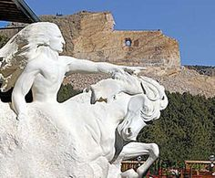 Crazy Horse Monument, South Dakota. The small design version is shown in front of the actual unfinished monument.
