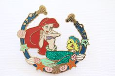 This retired Disney pin for sale features Princess Ariel with glitter tail and Flounder surrounded by a sea shell border. Very beautiful! Guaranteed Authentic and Scrapper-Free. Earn reward points on