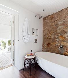 """Sandstone walls, white bath. """"I find it remarkable that someone, a long time ago, painstakingly quarried the sandstone by hand and lovingly built the gorgeous walls, each piece fitting together like a puzzle,"""""""