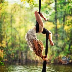 Appreciate that she's doing this upside down over a lake. How did she even get on?