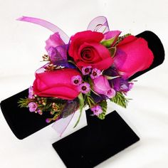Here's a pretty mix of hot pink roses & lavender spray roses, with a little wax flower.