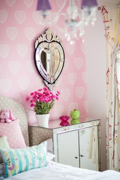 Pretty pink flowers and heart shaped mirror add to the design in the girl's bedroom