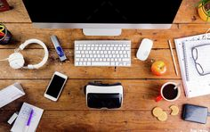 Desk with various gadgets and office supplies. Flat lay by halfpoint. Desk with various gadgets and office supplies. Computer, smart phone, virtual reality goggles and stationery around t...