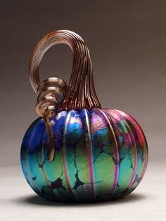 Our pumpkins are hand blown and one of a kind. We use only the finest quality glass and imported color glass in our work. There is no paint used in our process, the color is in the glass, meaning our pumpkins will not fade or chip over time. Our colors and designs are quite unique and are guaranteed to please you. They make great decorations on a bookshelf or a kitchen counter, and they make awesome gifts for loved ones! Sizes are approximately as follows:  Small (4.5H x 3.5W) Medium (5.5H x…
