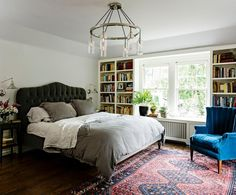 Book lover's bedroom features ring nickel and glass chandelier illuminating a charcoal gray velvet ...